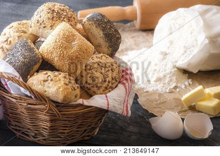 Basket with mixed buns and ingredients - Baking theme image with a wicker basket full of homemade bread rolls surrounded by flour eggshell butter and a rolling pin on a rustic wooden table.
