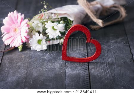 Bright red heart and a bouquet of flowers - Cute red wooden heart on a black vintage table with a blur cheerful bouquet of flowers wrapped in newspaper in the background.