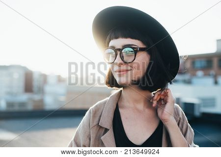 Portrait of beautiful dreamy and romantic young woman or teenager in hipster stylish fashion outfit with artisan tattoos on arm and nerdy glasses looks to side at sunset over city
