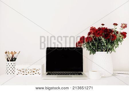 Home office desk with blank screen laptop beautiful red flowers bouquet white vintage casket in front of white background. Blog website or social media concept .