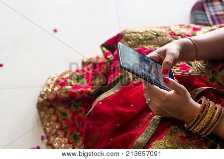 Over head view of a girl in traditional red indian saree and bangles using a mobile phone. Shows how even for traditional people the mobile is now a part of life