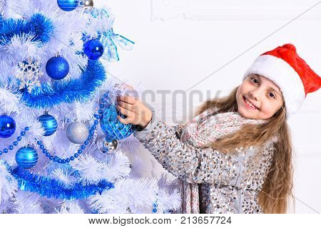 Miss Santa In Red Hat Near White Christmas Tree