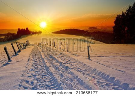 Snowy winter Christmas Landscape. Winter sunset with field road and sky.