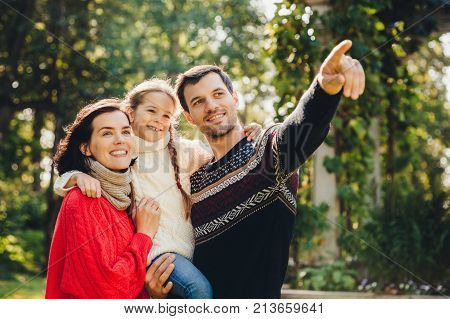 Outdoor portrait of smiling happy friendly family have walk together. Affectionate father shows his small daughter something into distance. Family admire sunrise, beautiful nature, wear warm clothes