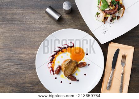 Roasted goose liver with date, apple and fruit and berry sauce painting with cutlery and seafood salad top view. Creative french cuisine, delicatessen restaurant meal