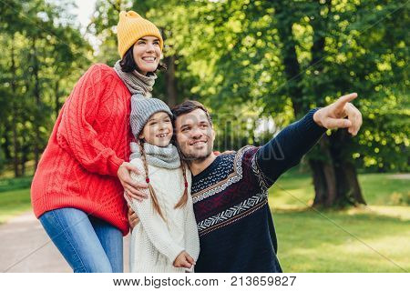 Three family members spend time together, look at beautiful lake in park, indicate with fingers, being in good mood, smile pleasantly. Father, mother and daughter enjoy togetherness, calm atmosphere