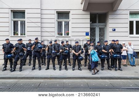 ZAGREB, CROATIA - JUNE 11, 2016: 15th Zagreb pride. Elderly woman passing by police cordon holding hands over ears.