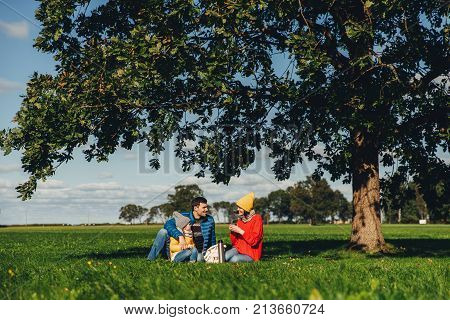 Happy family have autumn picnic, sit on green grass, drink hot tea, communicate with each other, enjoy calm atmosphere, admire blue sky and beautiful landscapes. Friendly family members together