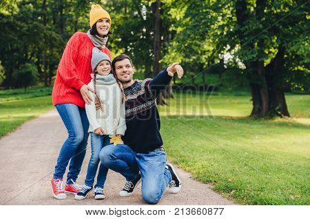 Pleasant looking dad shows with fore finger beautiful landscape to her daughter, embraces her. Family of three members have walk at park, have good relatioship, look into distance as notice something