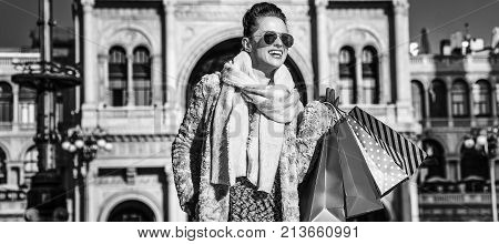 Rediscovering things everybody love in Milan. happy modern woman in fur coat and sunglasses near Galleria Vittorio Emanuele II in Milan Italy looking into the distance