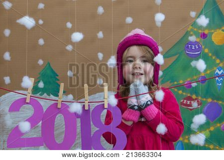 New Year 2018 concept. Beautiful small girl decorating the New Year numeral. against the background of a painted Christmas tree and snow