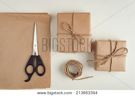 gift a surprise in the box is packed in brown vintage paper and tied with a rope scoop. Christmas concept. on a white homogeneous background.near the scissors