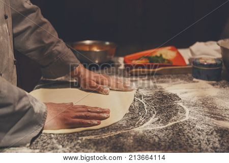 Hands kneading dough for pizza making. Chef preparing base for making traditional italian meal, copy space