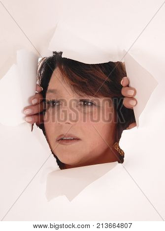 A pretty woman holding up a paper with a big hole and looking trough holding the hole open isolated for white background