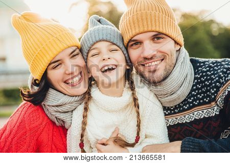 Happy girl with pigtails, wears warm knitted sweater, stands between father and mother, laugh happilly, have sincere smiles on their faces. Relaxed family have holidays, spend nice time together