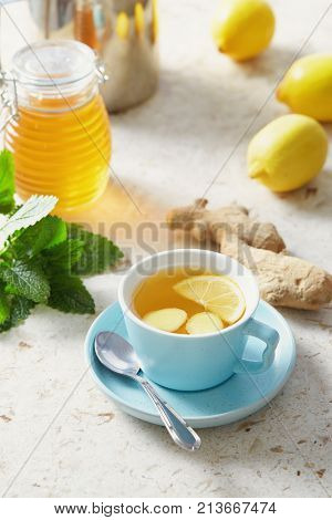 Lemon and ginger tea with honey. Cup of hot honey lemon tea with fresh ginger root.