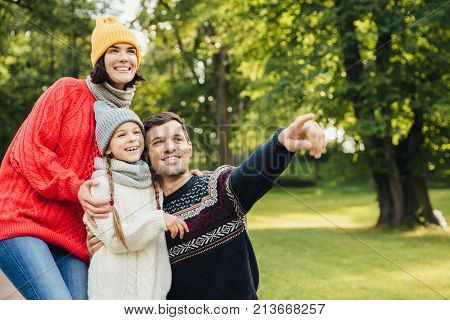 Family, season, relationship concept. Friendly affectionate family have walk at autumn park, admire beautiful nature, wear warm knitted clothes, point into distance as show something interesting