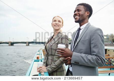 Happy man and woman in formalwear enjoying their business trip by steamship