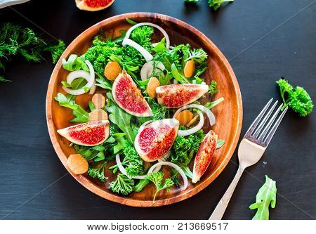 Autumn salad of arugula, figs in brown earthenware plate on a dark background. top view