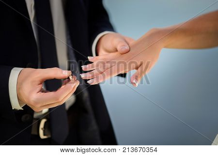 The bridegroom puts the ring on the bride.