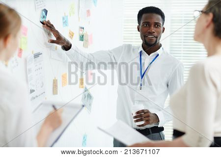Confident detective talking to his colleagues by whiteboard at meeting
