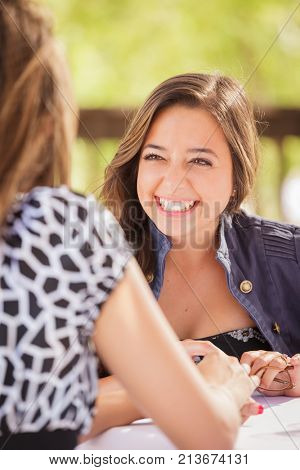Two Mixed Race Girlfriends Having A Conversation At An Outoor Patio Table