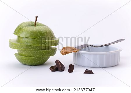 Green apple, chocolate, and peanut butter. A close up of a stacked sliced apple chocolate chunks and peanut butter.