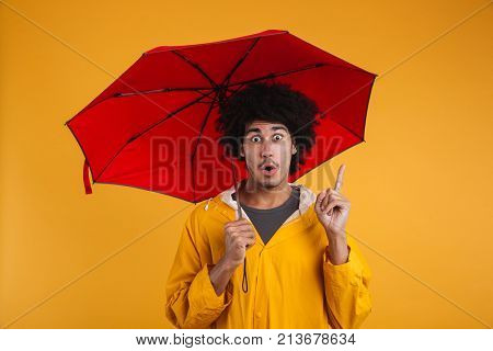 Portrait of a surprised young african man dressed in raincoat holding an umbrella and pointing finger up isolated over orange background