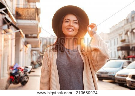 Happy attractive asian trendy woman adjusting her hat while walking on the city street