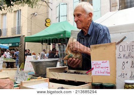 Pezenas, Herault, France - Aug 26 2017: Elderly But Cheerful Senior Man Working On A Market Stall Se