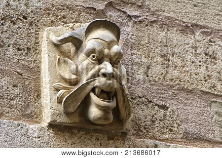 Pezenas, Herault, France - Aug 26 2017: Grotesque Carved Stone Gargoyle Head On A Stone Wall