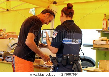 Valras-plage, Herault, France - Aug 25 2017: Female French Police Officer Buying Cheese From A Marke
