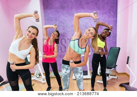 Four cheerful women holding dumbbells while doing exercises for arms and lateral abdominal muscles during group fitness, class in a modern health club for ladies only