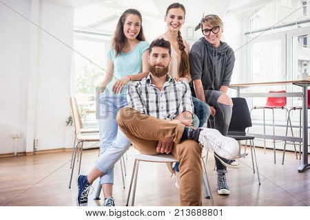 Portrait of four co-workers smiling and looking at camera while wearing cool casual clothes during work, in the shared office space of a modern hub for freelancers and young entrepreneurs