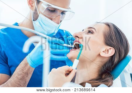 Side view close-up of a relaxed young woman during painless oral treatment in the modern dental office of an experienced and dedicated dentist