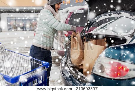 consumerism, transportation and people concept - female customer loading food from shopping cart to car trunk at winter parking over snow