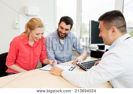 family planning, medicine, fertility and healthcare concept - happy couple visiting doctor and filling form at clinic