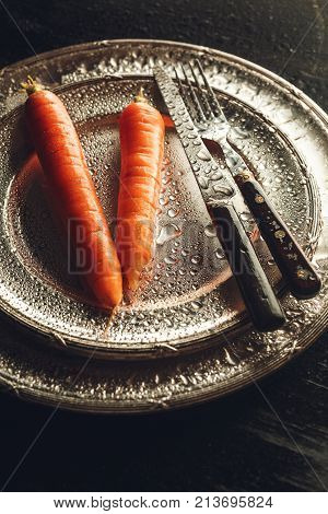 Fresh wet carrots on a shinny silver plate