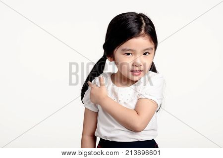 A studio portrait of an asian young girl pointing at something