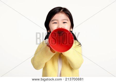 Studio portrait of an asian girl speaking with a loudspeaker
