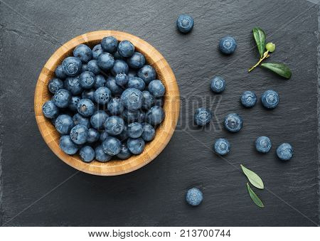 Fresh Blueberries with leaves in a bowl on dark stone background. Flat lay top view.