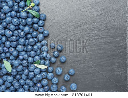Fresh Blueberries with leaves on dark stone background. Flat lay top view.