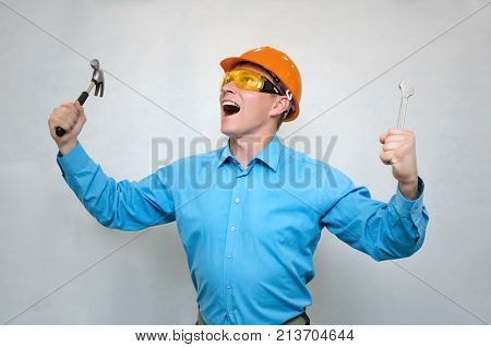 Crazy builder worker with hummer and wrench in his hand screams and looks up. Tired of work.