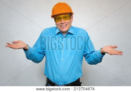 Confused builder engineer can not explain what happened and holds his palms up. The builder is stumped by someone's question. Construction incident.
