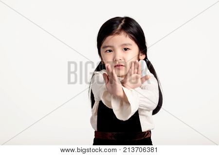Studio portrait of an asian girl rejecting something