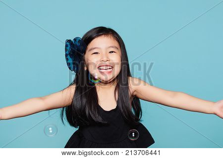 Studio portrait of asian girl with soap bubbles in front of blue background