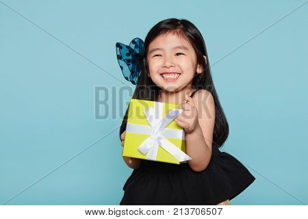 Studio portrait of asian girl happily receiving a gift
