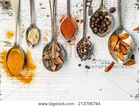 spices in spoons on old wooden background