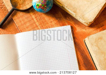 copy book, magnifying glass and globe on wooden table