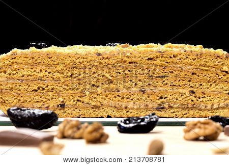 Delicious honey cake divided with prune and nuts on black background